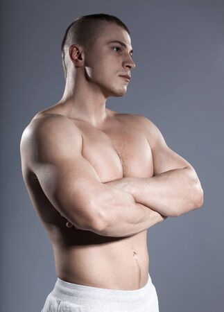 strong brutal short-hair man bodybuilder with muscular isolated on gray background