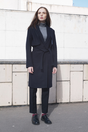 black boots: young female fashion model in classic navy trench coat, melange blouse and black boots - street style