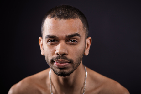 rapping: close up portrait of young attractive black man isolated on studio black background