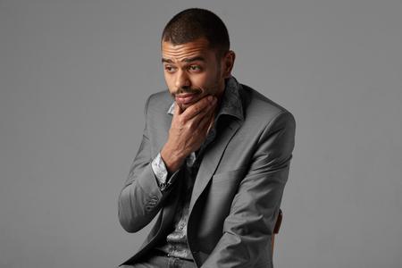 isolated on gray: thoughtful black man thinking in gray blazer isolated on studio gray background