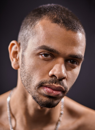 close up portrait of young attractive black man isolated on studio black background