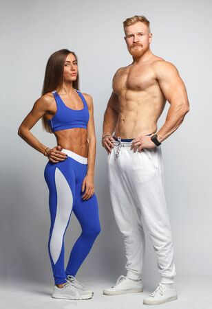 athletic body: young muscular sportsman with sexy sportswoman with athletic body isolated on gray background Stock Photo