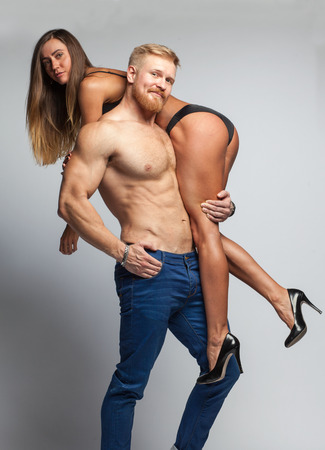 strong muscular bearded man hold up sexy young woman in lingerie isolated on gray background