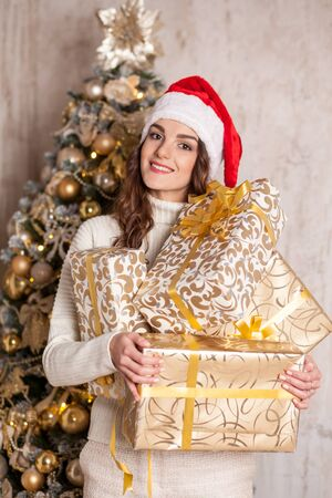 young smiling brunette woman with many gift boxes near Christmas tree Stock Photo