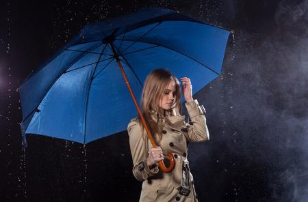 Mujer rubia joven con impermeable clásico con el paraguas en la lluvia aislada en fondo negro