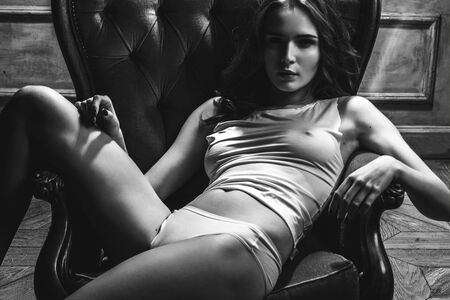 seduce: monochrome portrait of sexy woman in underwear sitting in chair Stock Photo