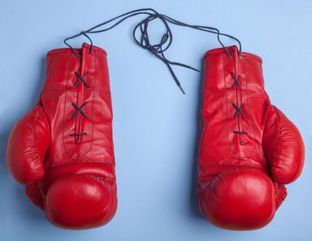 red boxing gloves with copy space in center isolated on blue background