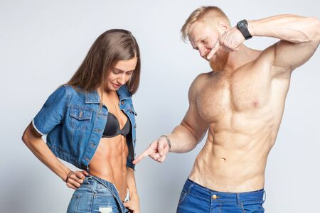bearded muscular man shows perfect muscular abs of her sporty girlfriend sportswoman isolated on studio background Stock Photo