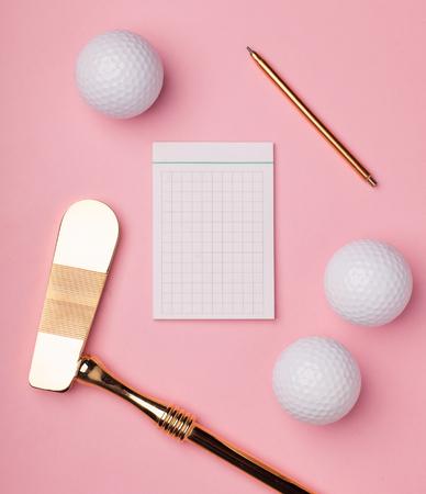 Notepad vuoto circondato golf club di lusso dorato con palline da golf isolato su sfondo rosa Archivio Fotografico - 78340002