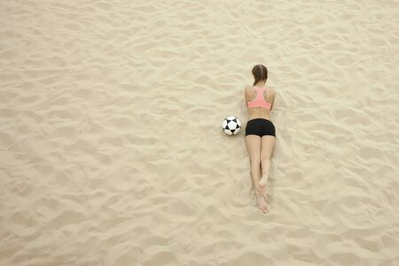 young sportswoman with ball lay on sand Imagens