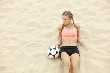 laying abs exercise: young sportswoman with ball lay on sand Stock Photo
