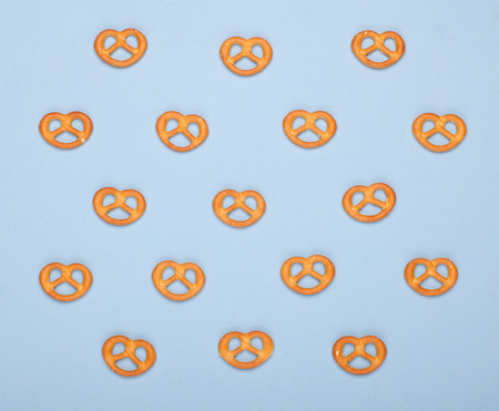 pattern of many PRETZELS bakery on blue background, top view photo