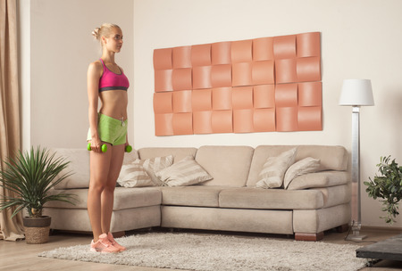 Young sporty caucasian female with dumbbells in initial position for lunge exercise at home interior Stock Photo