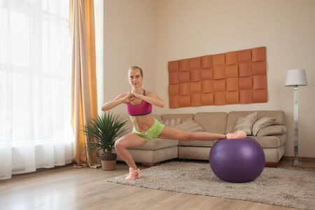 young blonde woman doing stretching exercise with fit-ball indoor at home interior Stock Photo - 84472455