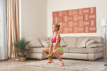 young blonde sportswoman doing squats with dumbbells indoor, home interior