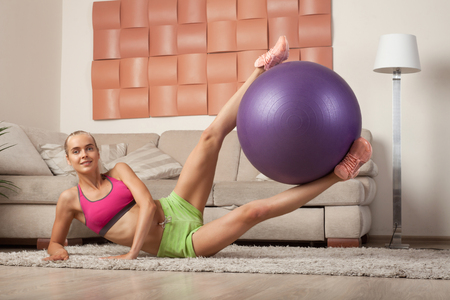 smiling fit blonde woman do exercise with fit-ball at home Stock Photo