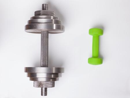 大きな重い鋼鉄ダンベルは白で隔離された小さい緑色のライトダンベルと比較する