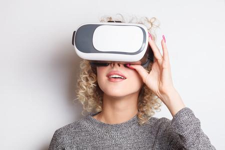 vroeg me af blonde jonge blanke vrouw met virtual reality-bril Stockfoto