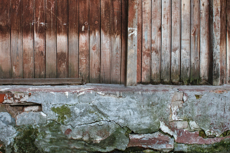 old wooden wall with chapped stone basement