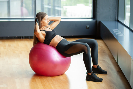 athletic woman in gym doing abs exrcise on fitness ball
