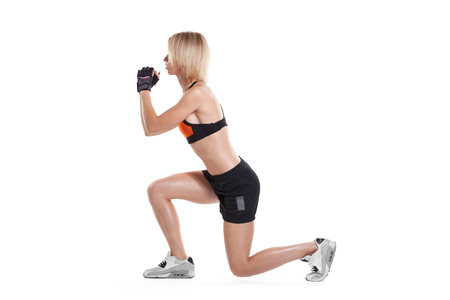 slim blonde woman doing lunge exercise isolated on white background