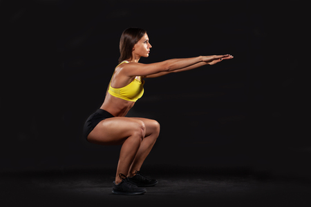 brunette muscular woman doing squats isolated on black background