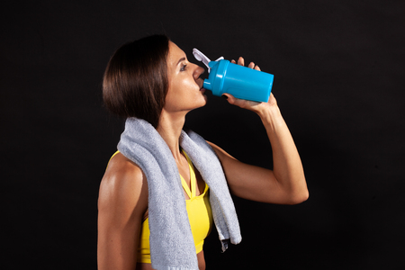young woman in sportswear and towel drinking from sportive shaker isolated on background