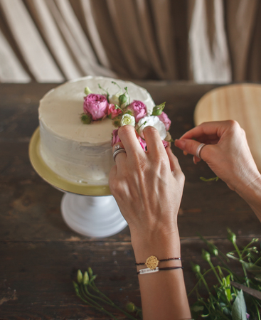female hands decorating white cream cake with flowers, natural light, POV