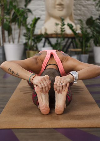 tattooed woman doing stretching exercise - asana Paschimottanasana in yoga class