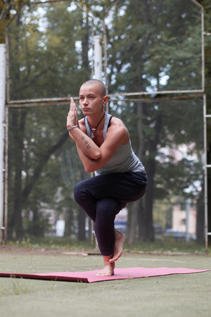 skinhead tattooed woman in yoga eagle pose, Garudasana, outdoor, summer day Imagens