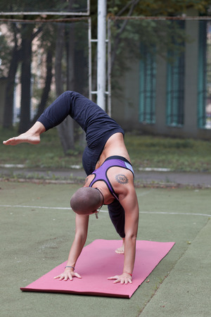 athletic tattoed woman doing yoga asana outdoor in spring park Imagens