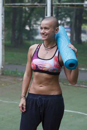 smiling skinhead woman with yoga carpet standing in summer green park