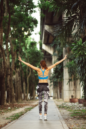 young sportswoman walking city streets, throwing hands up, finishing her outdoor workout