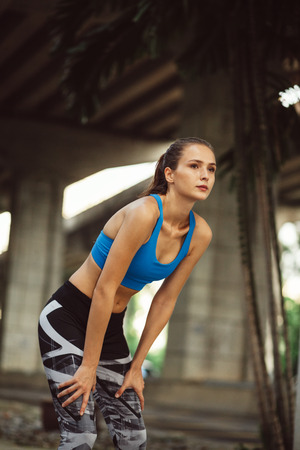 young slim woman in sportswear resting after outdoor workout in urban space Stock Photo