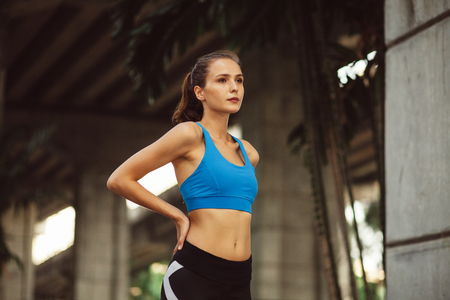 young athletic woman standing ready to outdoor workout in urban city