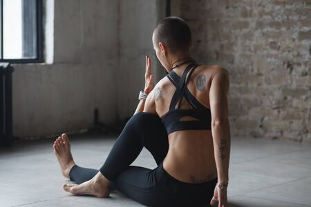 young skinhead woman doing twist stretching yoga exercise - ardha matsyendrasana indoor 版權商用圖片