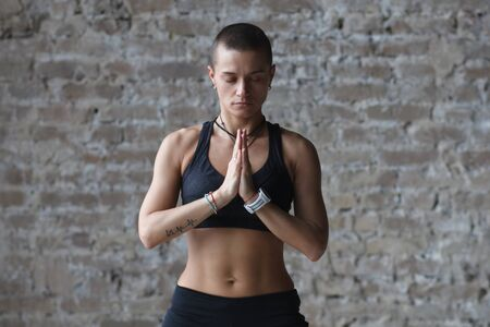 Young Woman Meditating with hands together near brick wall Imagens - 124955891