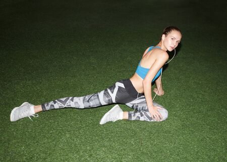 young fitness woman warming up before workout, stretching legs, on green lawn, direct flash light