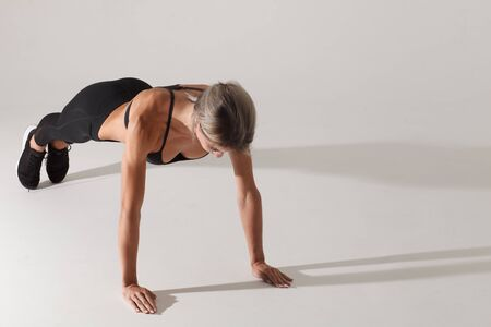 athletic blonde sportswoman doing plank exercise isolated on white background with shadow Stock Photo - 129521659