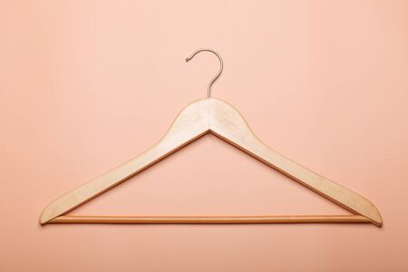 one beige wooden clothes hanger isolated on brown background