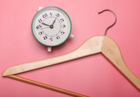 brown wooden clothes hanger near vintage alarm clock  isolated on pink background, sale concept