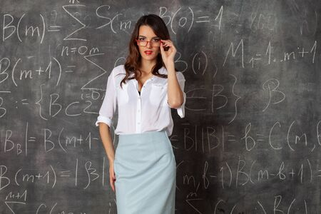young smart woman with glasses near blackboard with maths formulas