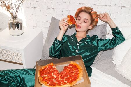 young fashionable woman in silk pajamas lays on bed and eat pizza pepperoni from pizza box, direct flash