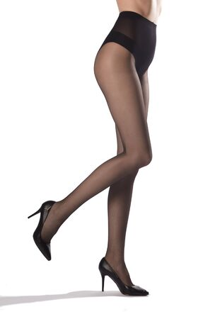 caucasian female long slim legs in black tights and black shoes isolated on white background
