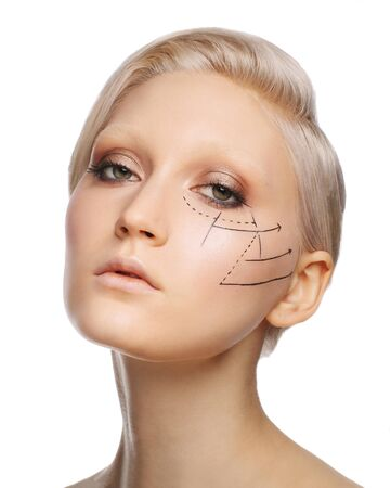 Pretty fashionable white blonde girl with perforation lines on face, plastic surgery concept, close up portrait