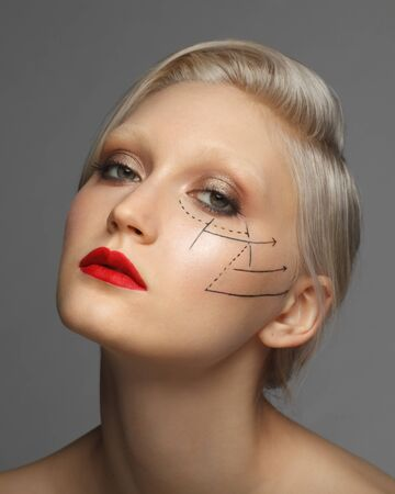 beautiful woman with perforation lines on her face, on studio background, plastic surgery concept