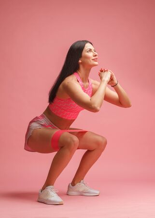 athletic woman in pink sportswear doing squat exercise with fitness loop on pink background Stock fotó