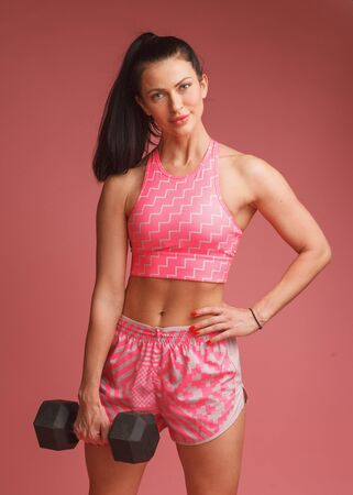 muscular brunettte woman standing with heavy dumbbell isolated on pink background