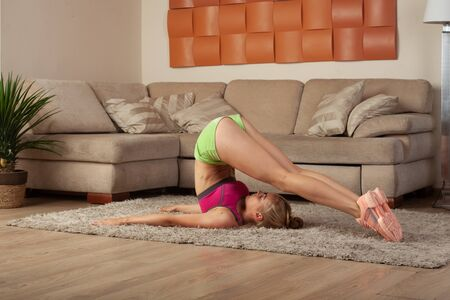 young beautiful blonde female in sportswear stretching legs on home workout