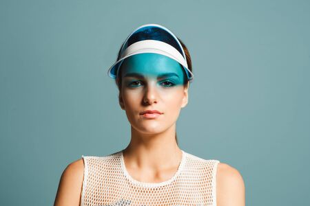 attractive young woman with sunvisor isolated on blue background, close up